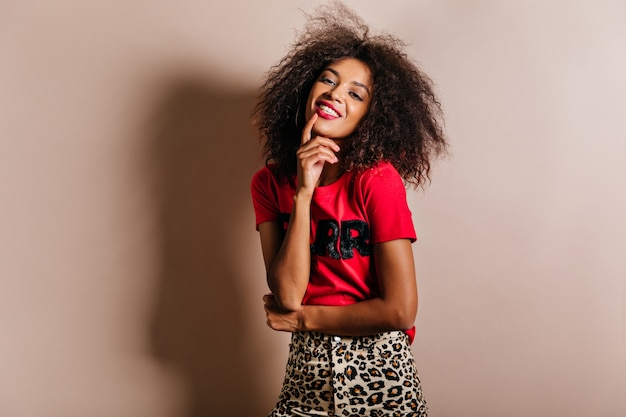 Mulher jovem sorridente em uma camiseta rosa da moda rindo na parede bege
