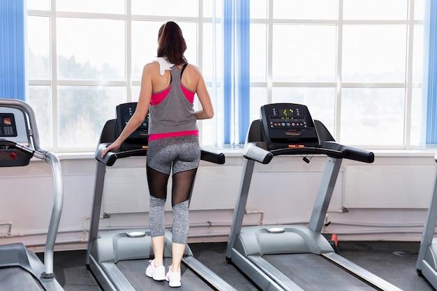 Mulher jovem sorridente em uma esteira na academia. estilo de vida ativo e saúde. vista traseira.