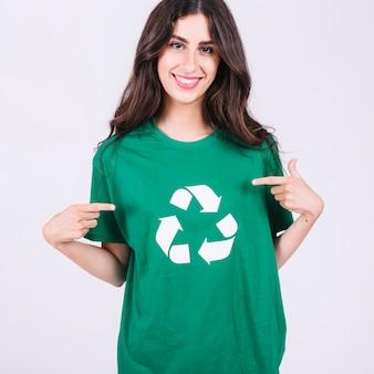 Mulher jovem sorridente, em, verde, t-shirt, mostrando, recicle ícone