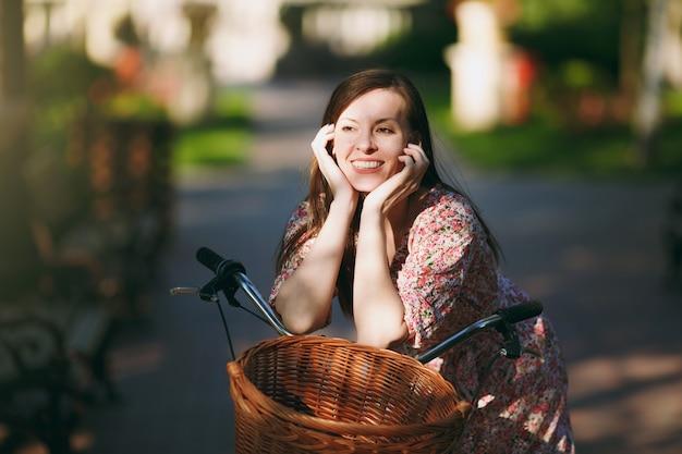 Mulher jovem sorridente em vestido floral rosa longo parar de andar em bicicleta vintage com cesta para compras, comida ou flores ao ar livre, lindo tempo de recreação feminino atraente na primavera ou parque de verão.