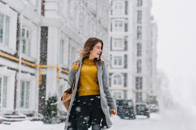 Mulher jovem sorridente encantadora no casaco com mochila andando na queda de neve no centro da cidade da europa. expressar positividade, emoções verdadeiras, desfrutar nevando, esperando as férias de natal, sorrindo para o lado.