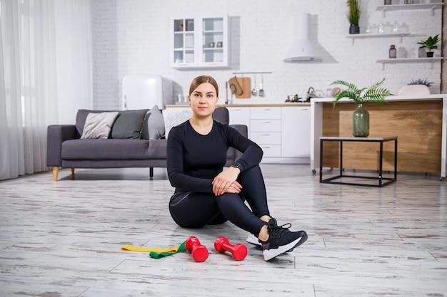 Mulher jovem sorridente, exercitando-se com elástico no treino de fitness em casa. conceito de estilo de vida saudável. esportes em casa durante a quarentena