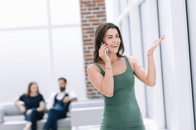 Mulher jovem sorridente, falando em um celular. foto com espaço de cópia