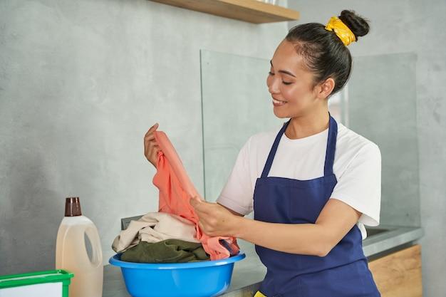 Mulher jovem sorridente, faxineira satisfeita com a qualidade da roupa lavada em casa. conceito de serviço de limpeza profissional para residências