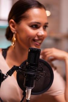 Mulher jovem sorridente fazendo gravação de podcast para programa online em estúdio caseiro