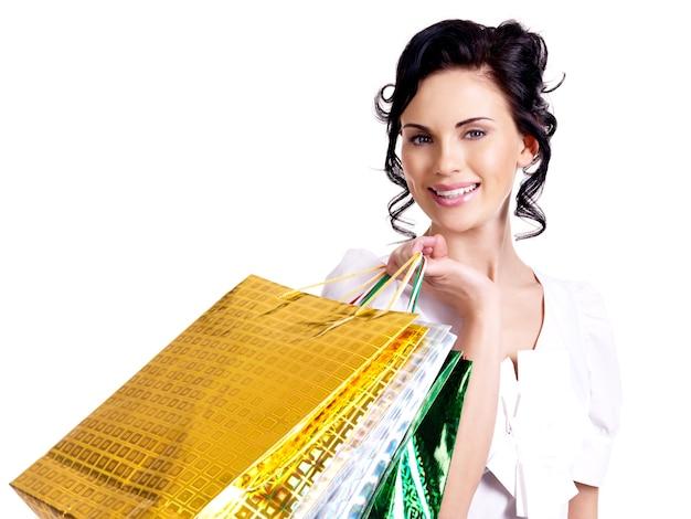 Mulher jovem sorridente feliz com sacos coloridos, olhando para a câmera - isolada no branco.