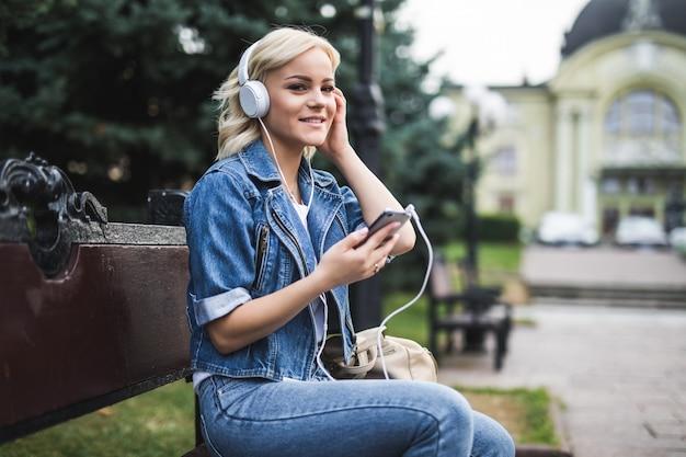 Mulher jovem sorridente feliz ouvindo música em fones de ouvido e usando o smartphone enquanto está sentado no banco da cidade