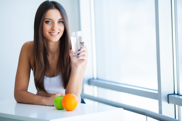 Mulher jovem sorridente feliz tomando suplemento dietético