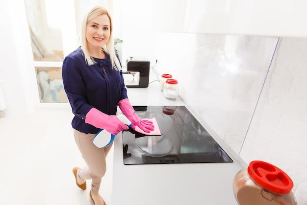 Mulher jovem sorridente limpa o limpador de fogão moderno na casa dele
