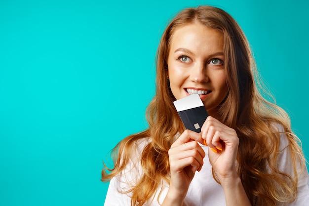 Mulher jovem sorridente mordendo um cartão de crédito na tentação de fazer compras contra um fundo azul