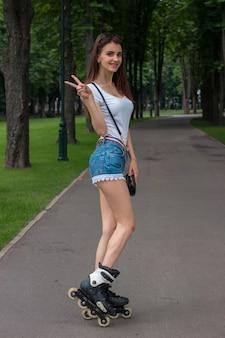 Mulher jovem sorridente mostra um gesto de mão com dois dedos e fica em pé sobre os rolos