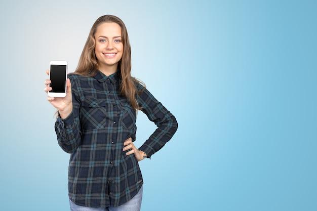 Mulher jovem sorridente, mostrando a tela do smartphone em branco