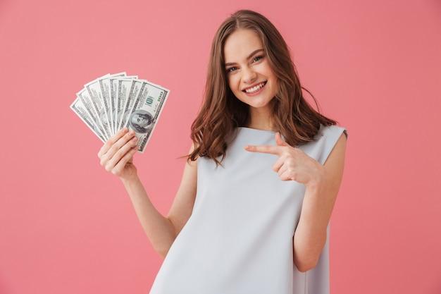 Mulher jovem sorridente mostrando dinheiro apontando.