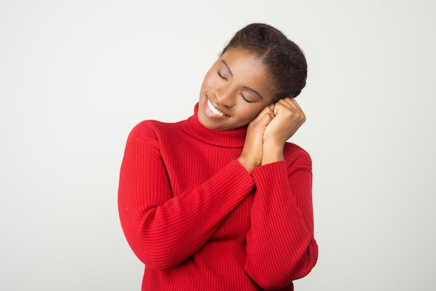 Mulher jovem sorridente, mostrando o gesto do sono