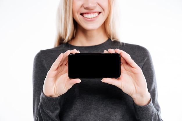 Mulher jovem sorridente, mostrando o telefone móvel de tela em branco para a câmera