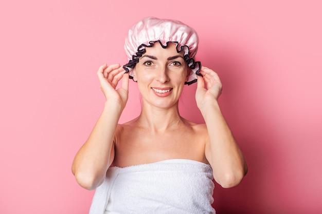 Mulher jovem sorridente na touca de banho rosa em fundo rosa.