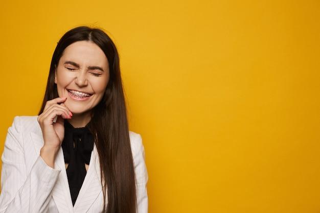 Mulher jovem sorridente no aparelho dental posando com os olhos fechados