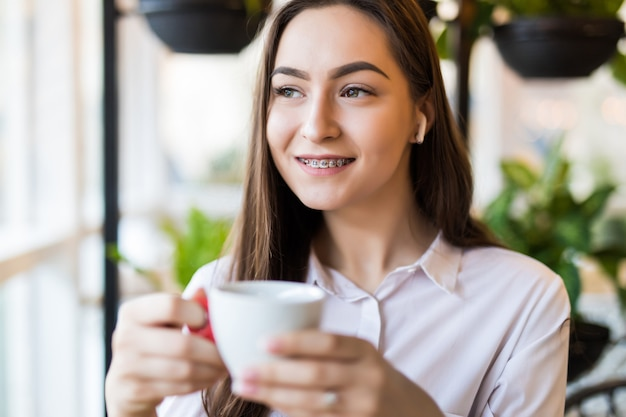 Mulher jovem sorridente no café com fones de ouvido, ouvindo música ou falando ao telefone