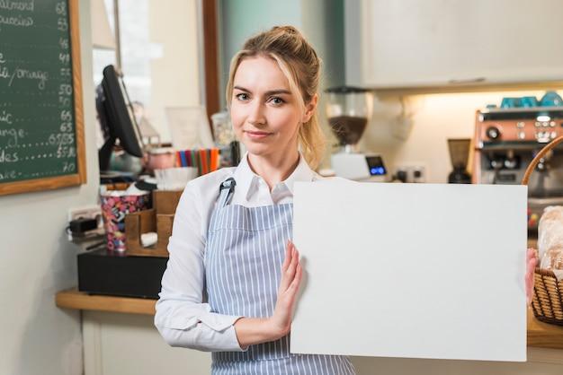 Mulher jovem sorridente no café mostrando a tela branca em branco