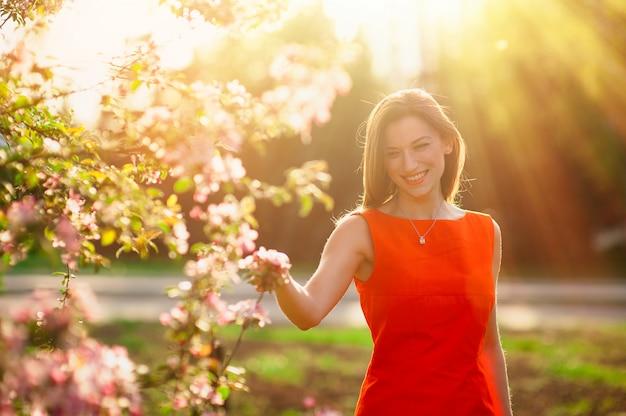 Mulher jovem sorridente no campo de árvores floridas primavera