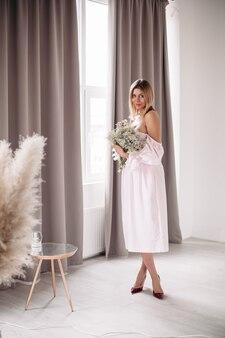Mulher jovem sorridente num vestido, aproveitando o dia com flores