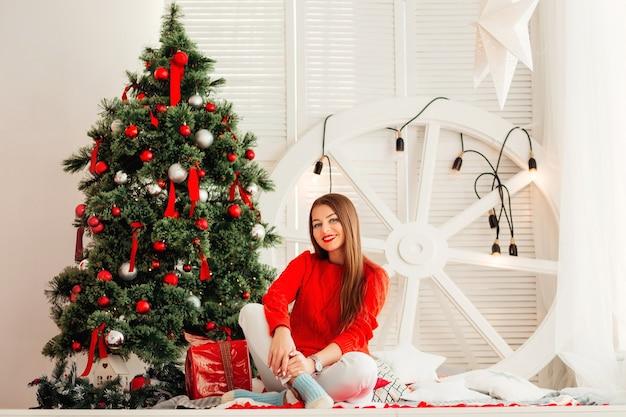 Mulher jovem sorridente olha para a câmera e se senta perto das decorações de ano novo