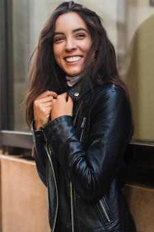 Mulher jovem sorridente, olhando para a câmera vestindo a jaqueta preta