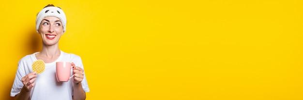 Mulher jovem sorridente, olhando para o lado com uma xícara de café e um waffle belga em um fundo amarelo. bandeira.