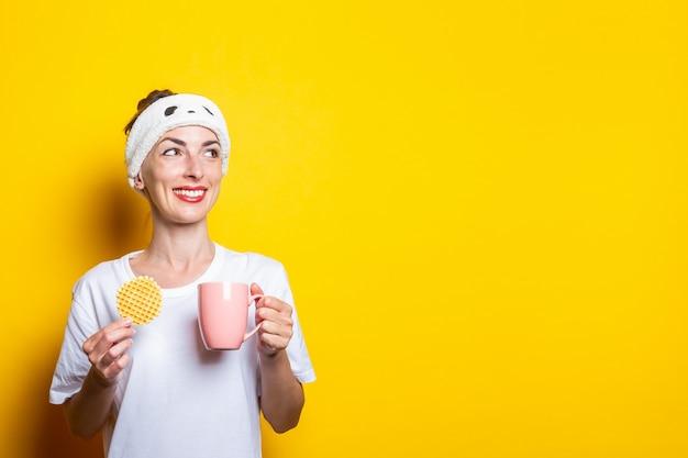Mulher jovem sorridente, olhando para o lado com uma xícara de café e um waffle belga em um fundo amarelo.
