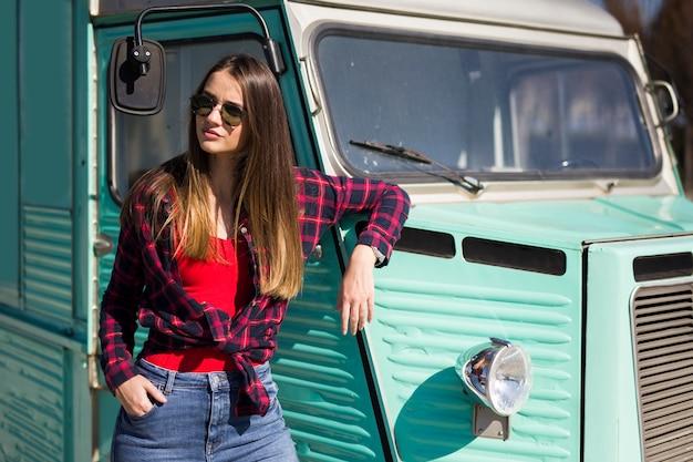 Mulher jovem sorridente pela minivan vintage