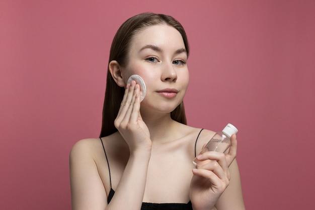 Mulher jovem sorridente, removendo a maquiagem com algodão, segurando a garrafa de água micelar no fundo rosa. rosto de limpeza de menina. produtos de tratamento e cosmetologia saudáveis. rotina de beleza, cuidados com a pele