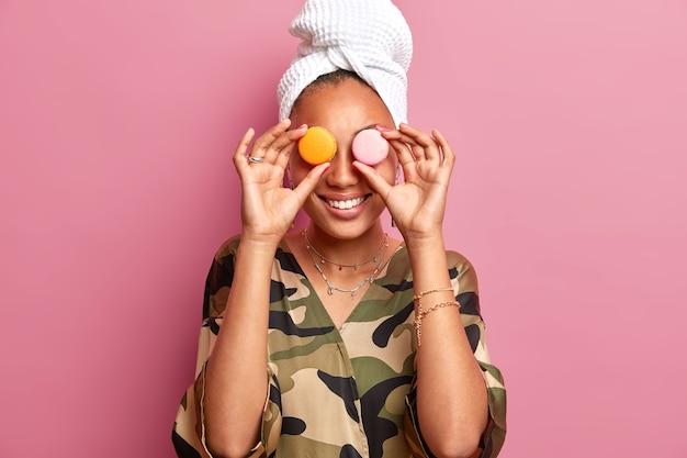 Mulher jovem sorridente satisfeita cobre macaroons doces sobre olhos de bom humor usa roupão e toalha enrolada na cabeça tem humor feliz isolado sobre parede rosa. conceito de junk food.