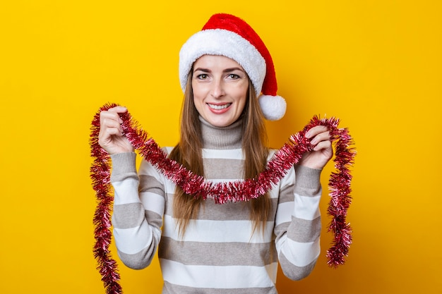 Mulher jovem sorridente segurando enfeites vermelhos de natal para decoração em fundo amarelo.