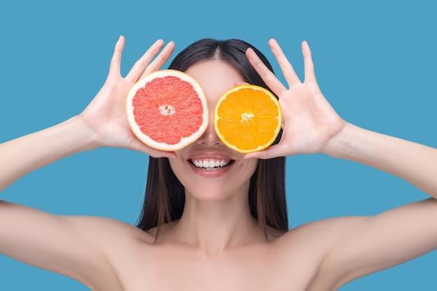 Mulher jovem sorridente segurando fatias de laranja e toranja