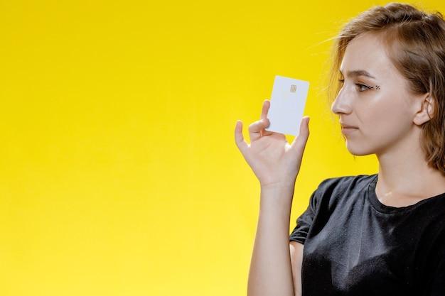 Mulher jovem sorridente segurando o cartão de crédito em fundo amarelo.