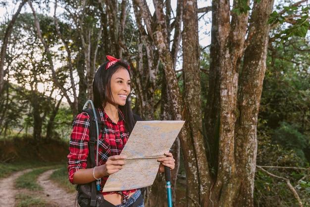 Mulher jovem sorridente segurando o mapa na floresta