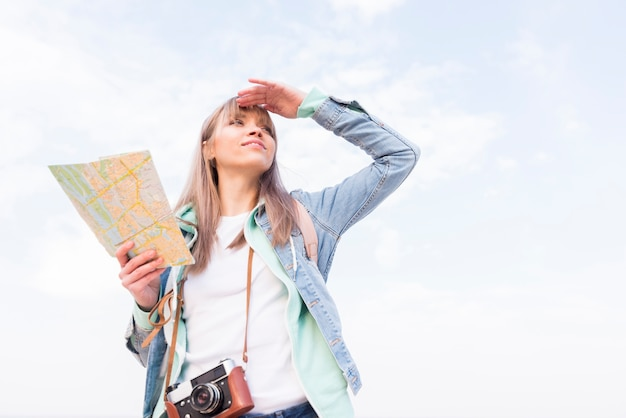 Mulher jovem sorridente segurando o mapa na mão, protegendo os olhos dela