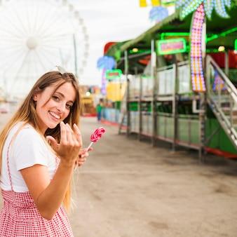 Mulher jovem sorridente segurando pirulito convidando alguém para vir no parque de diversões