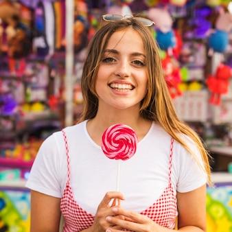 Mulher jovem sorridente segurando pirulito na mão