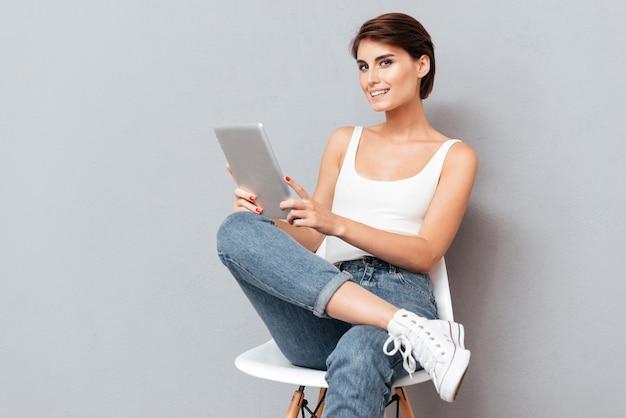 Mulher jovem sorridente segurando um computador tablet pc isolado no fundo cinza