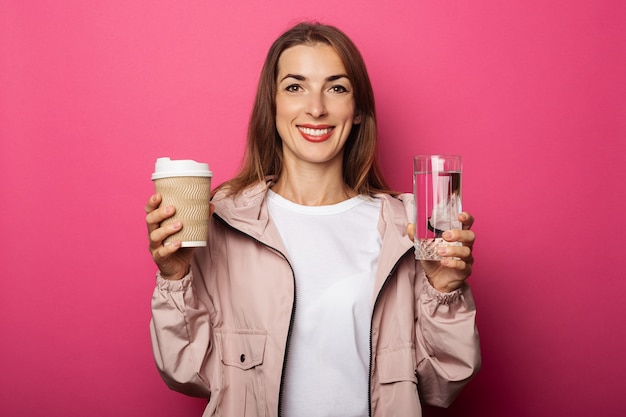 Mulher jovem sorridente segurando um copo de papel e um copo de vidro com água na superfície rosa