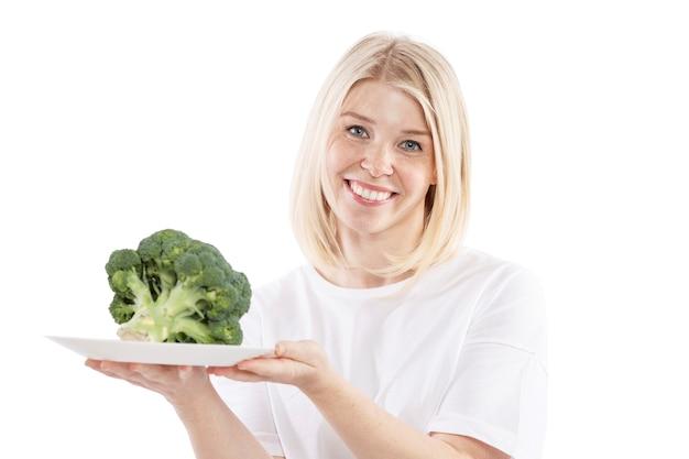 Mulher jovem sorridente, segurando um prato de brócolis nas mãos dela. vegetarianismo e dieta de alimentos crus. saúde e nutrição adequada. isolado sobre o fundo branco