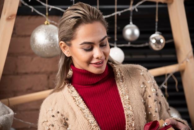 Mulher jovem sorridente segurando um presente de natal em um fundo de bolas de natal
