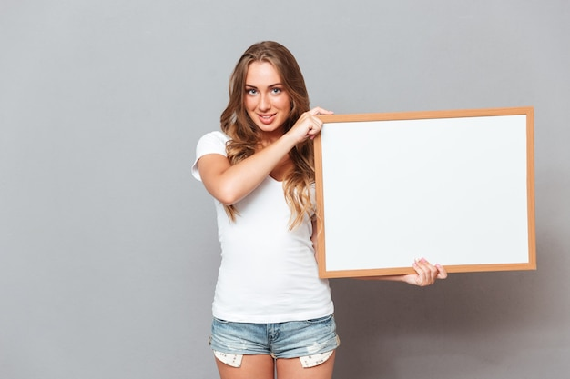 Mulher jovem sorridente segurando um quadro em branco sobre uma parede cinza