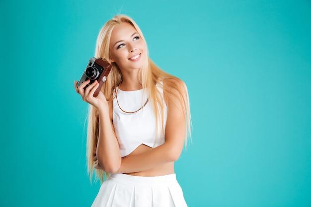 Mulher jovem sorridente segurando uma câmera retro e olhando para longe, isolada no fundo azul