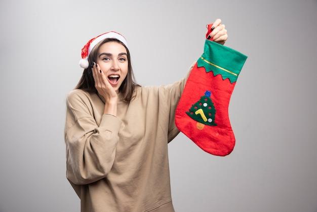 Mulher jovem sorridente segurando uma meias de natal.