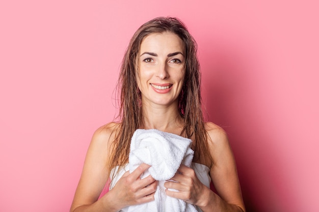 Mulher jovem sorridente segurando uma toalha com o cabelo molhado em um fundo rosa.
