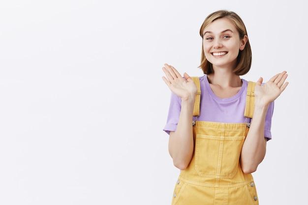 Mulher jovem sorridente sem noção levantando as mãos sem perceber