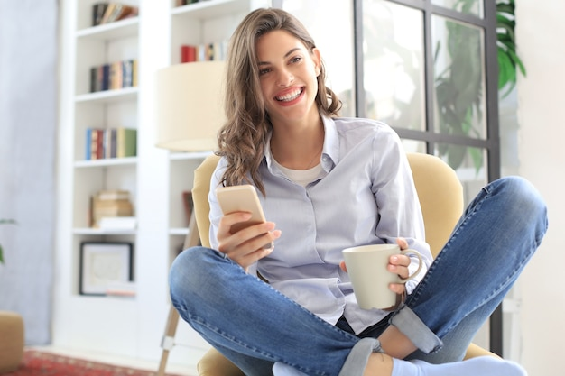 Mulher jovem sorridente, sentada na poltrona da sala de estar e usando com seu telefone celular.