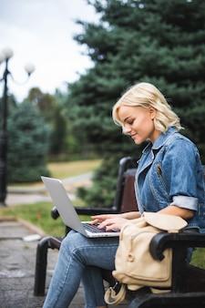 Mulher jovem sorridente sentada no banco e usar telefone e laptop na cidade de manhã de outono